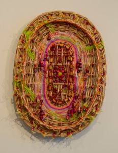 """Complications"" by Louise Roby.  Materials: Basket lid, beads & string.  21"" x 16"""