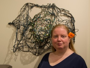 "Curator Crystal Edwards with her piece ""Galaxy"" made from painted yarn."